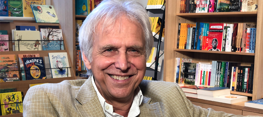 Mark Rubbo looking at the camera with publications in the background