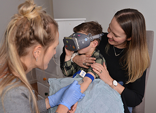 Child wearing the goggles whilst being held by his mother. The nurse is taking a blood test of the child distracted the vision in the goggles.